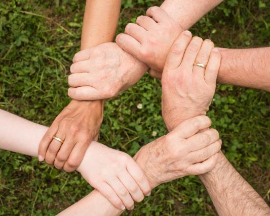 6人が互いの手首を順に繋いで、星形になっている画像