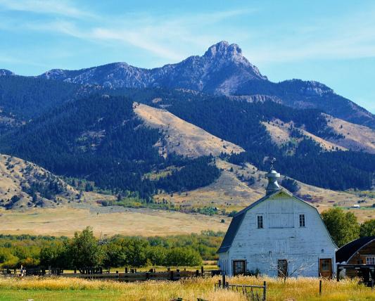 山のふもとの牧場の画像。右に白い小屋