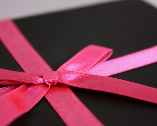 黒い箱にピンクのリボンをかけているプレゼント