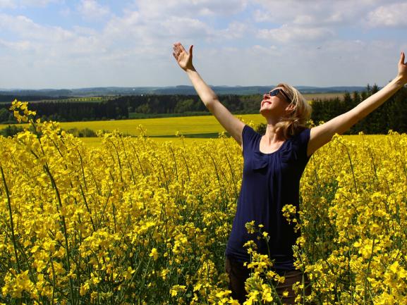 菜の花畑で両手を上げて喜ぶ女性