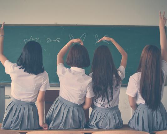 背を向けて机に座っている4人の制服姿の女子