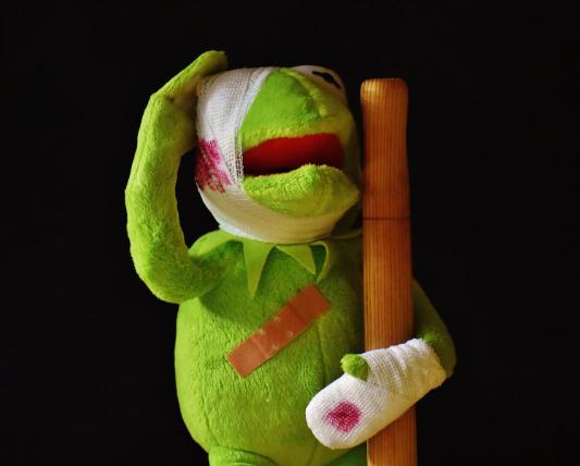 頭と左手をケガして杖をついているカエルのぬいぐるみ