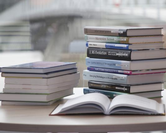 机の上に本の山が2つある画像