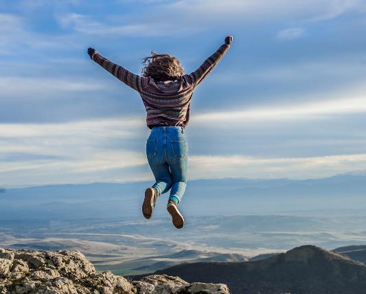 崖の上でジャンプしている女性の画像