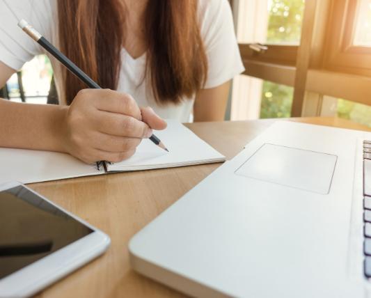 机の前にスマホとpcを置いてノートを取っている女性の画像