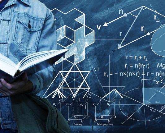 数式が書いてある黒板の左前に人が本を持って立っている画像