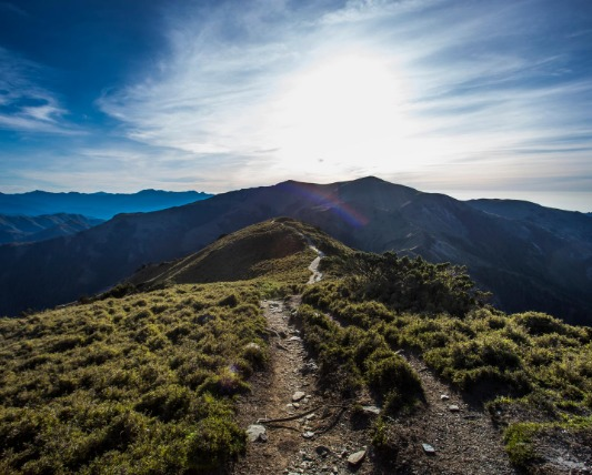 曇り空の下に広がる山に向かって続く山道の画像