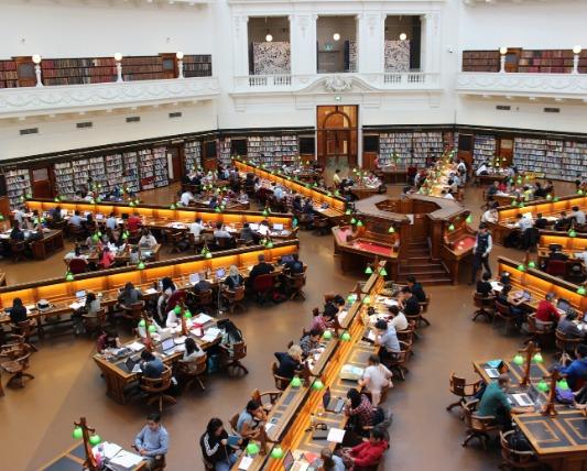 大きな図書館 放射線状に机が並んでいる画像