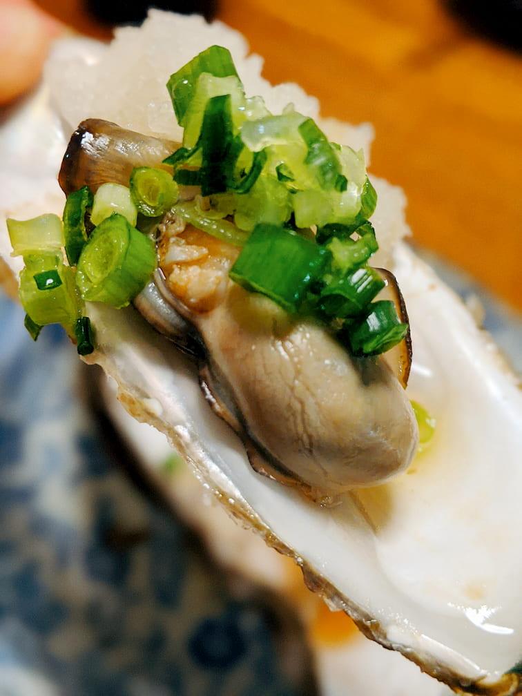 殻の上に乗った牡蠣に青ネギと大根おろしを乗せた画像
