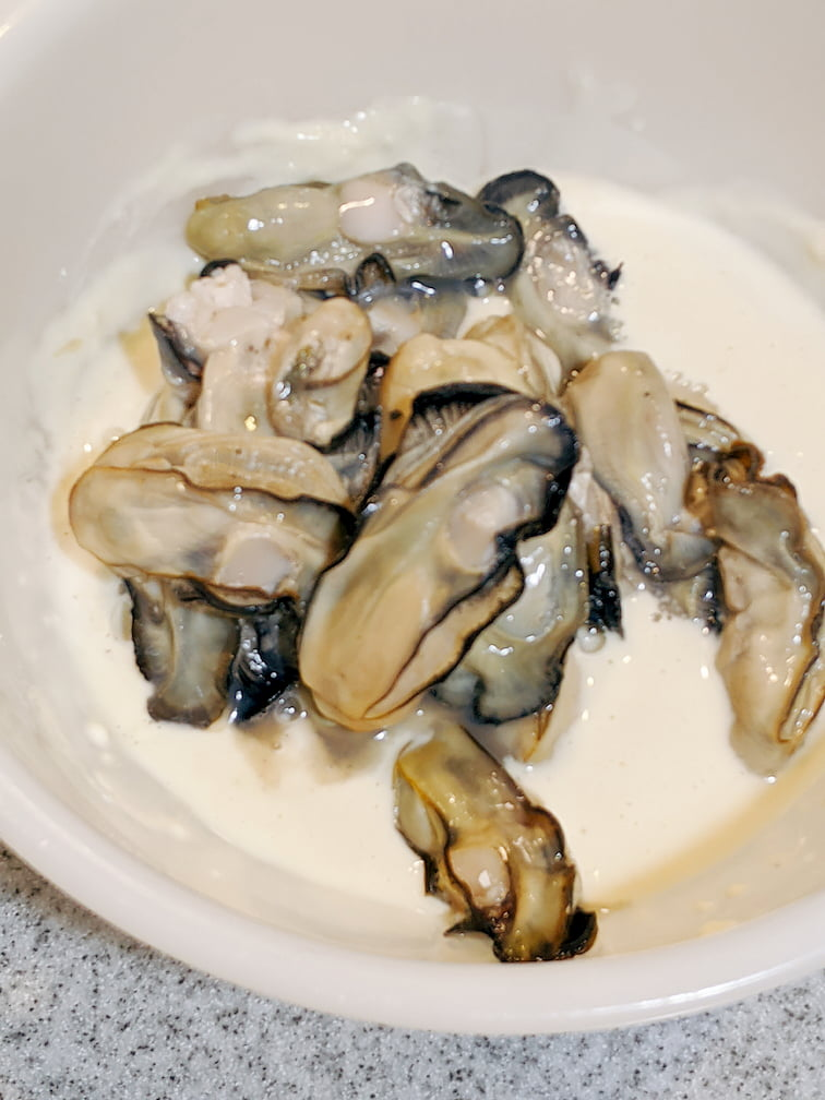ボウルに入れた水溶き小麦粉に牡蠣18個を入れた画像