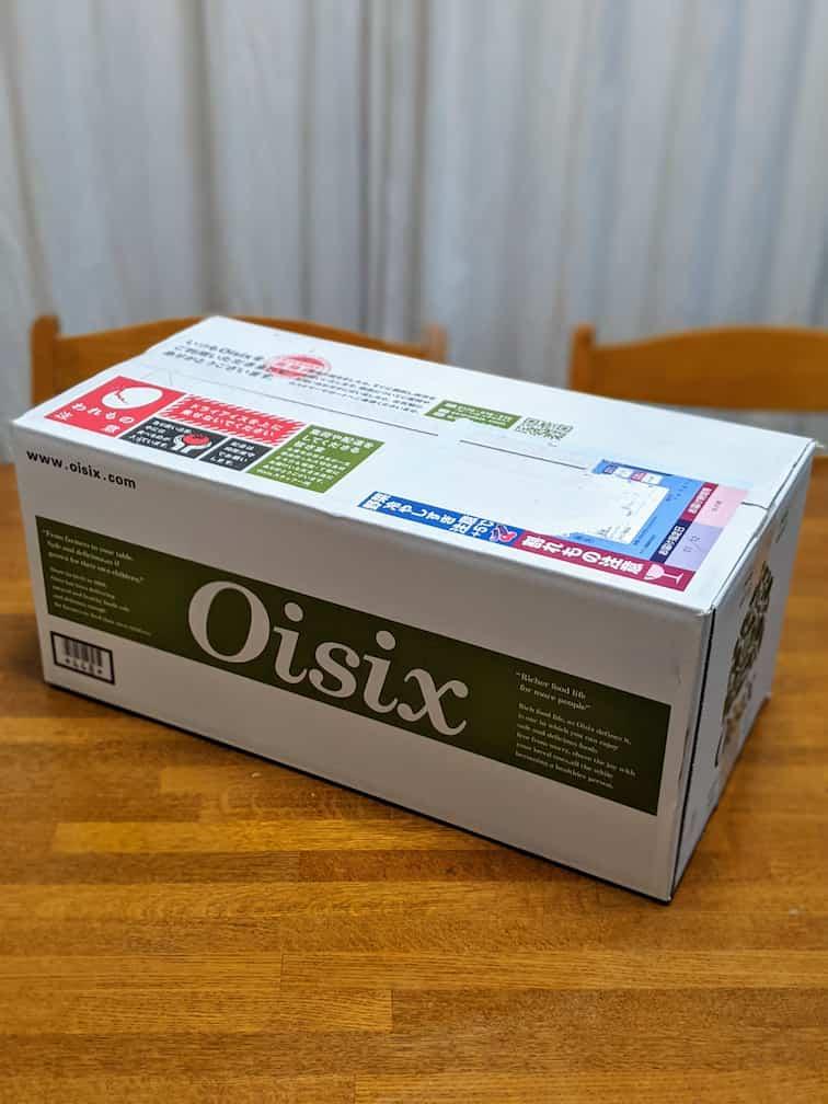 オイシックスの配送用段ボール 白地にグリーンの帯に白でoisixのロゴ入り