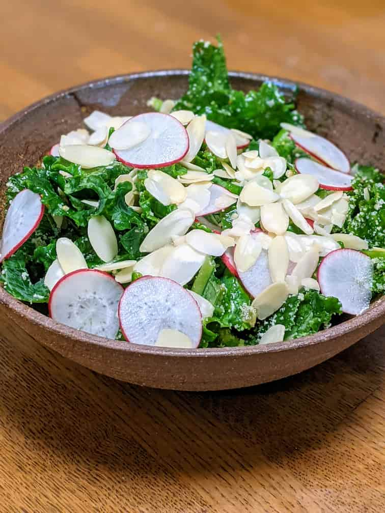 キットオイシックスケールのサラダ完成画像 茶色の器にケール・ラディッシュの輪切り・アーモンドスライスと粉チーズをまぶしている