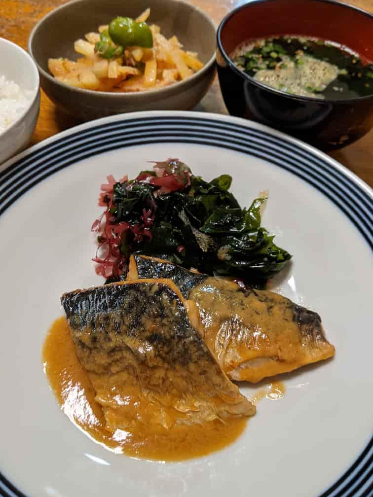 中央の皿の手前にサバの味噌煮2切れ、奥にわかめと海藻の和え物、奥にじゃがいもとピーマンのきんぴら、わかめスープの画像