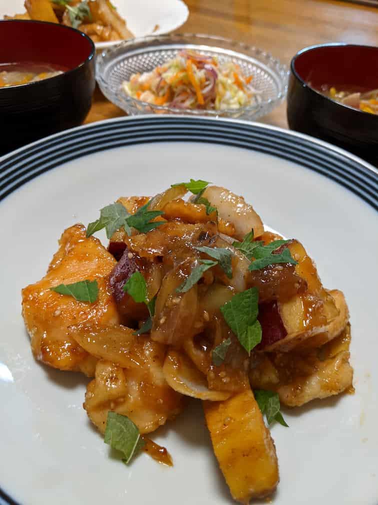 中央の皿にさつまいもと鶏肉を甘辛く炒めて上に大葉を散らしたもの、奥にしらす入りコールスロー、スープの画像