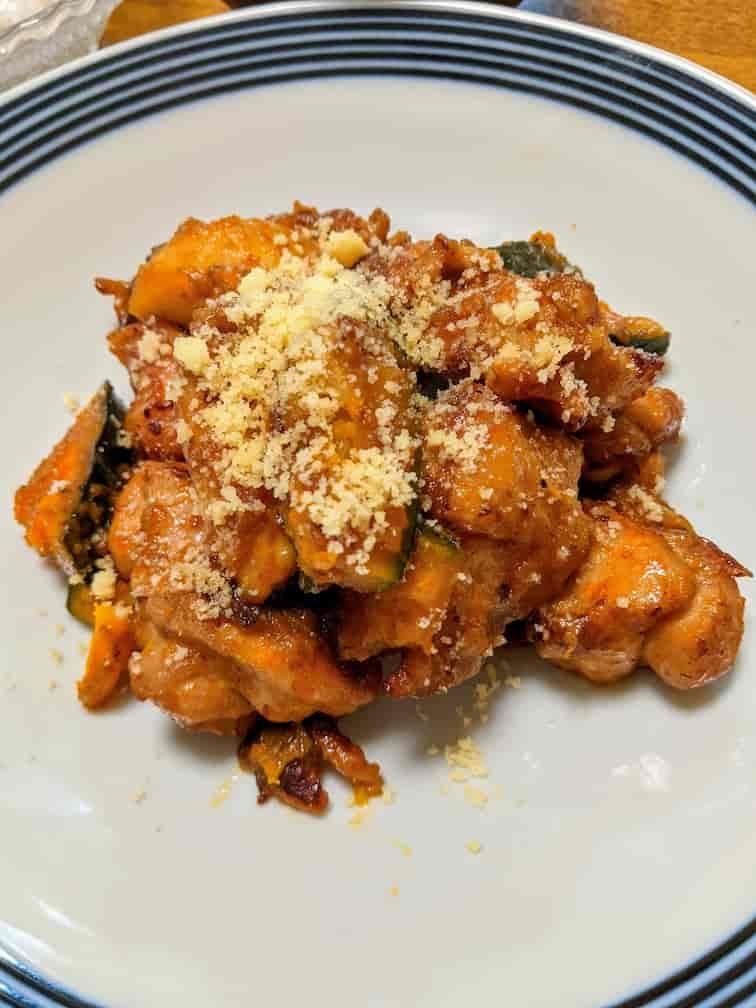 白いお皿に鶏肉とかぼちゃをバルサミコソースで炒めて上に粉チーズをかけた画像