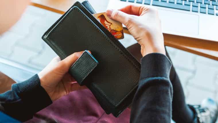 パソコンデスクの前に座った人が黒い長財布からクレジットカードを出している画像